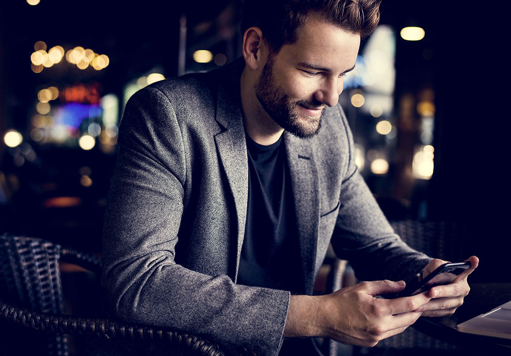 man looking at dating forums on his cell phone