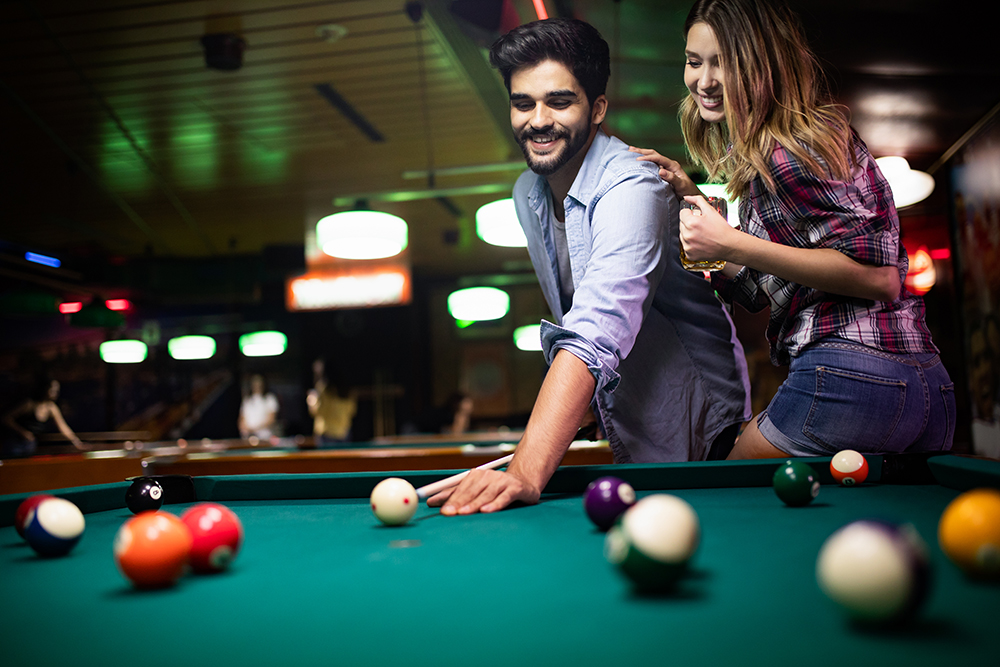 a couple playing pool and being part of the casual dating site community